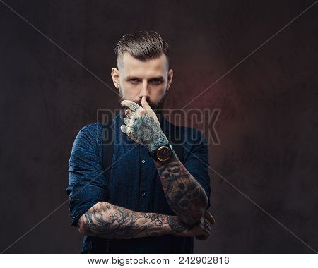 Severe Old-fashioned Hipster Guy In A Blue Shirt And Suspenders, Posing In A Studio. Isolated On A D