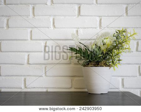 Front View Of Plant And Flower Mock-up In White Flowerpot On Wooden Desk In Front Of White Brick Wal