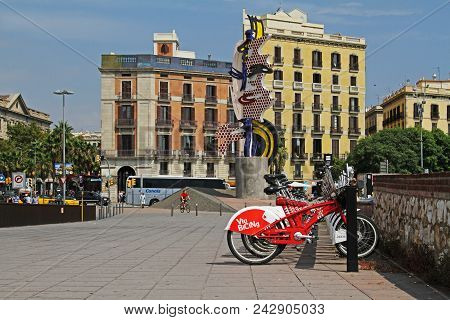 Barcelona, Spain - September 14, 2014: City Bicycles Stand In A Row On A Parking For Rent Against Th