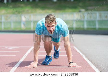 Man Runner On Start Position At Stadium. Runner In Start Pose On Running Surface. Man Run Outdoor At