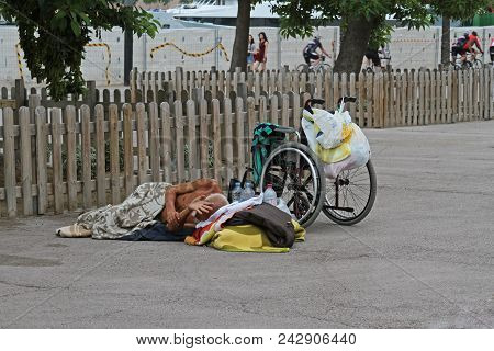 Barcelona, Spain - September 14, 2014: A Homeless Disabled Person With A Wheelchair Sleeping On The