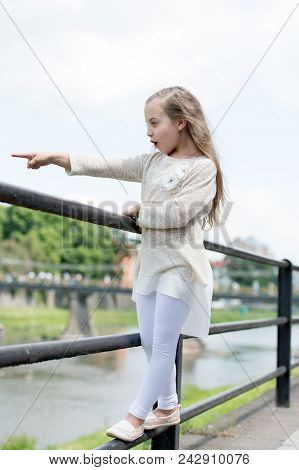 Kid Girl With Long Hair Walks Near Riverside, River On Background. Girl Child Tourist Enjoy Sightsee