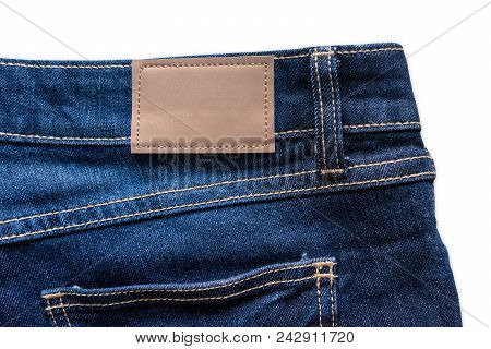 Back Of Blue Jeans With Leather Jeans Label Sewed On Blue Jeans. Isolated On White Background With C