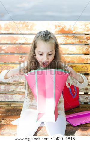 Girl On Surprised Face Unpacking Shopping Bags Or Presents, Bench On Background. Kid Girl With Long