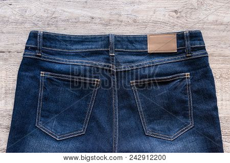 Blue Jeans On Wood Background With Leather Label.
