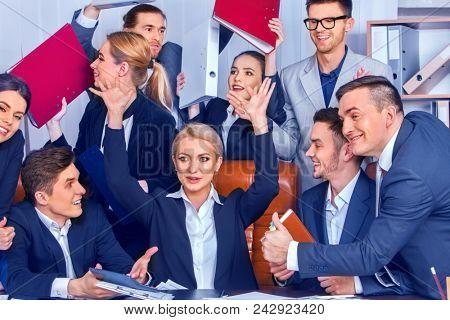 Business people office life of team people are happy with hand up sitting table and working papers . Cabinets with folders and jalousie background. Specialists in management.