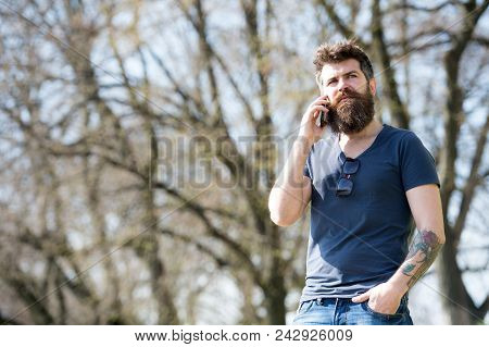 Hipster With Beard Speak On Mobile Phone Outdoor. Man With Beard And Mustache On Strict Face Talking