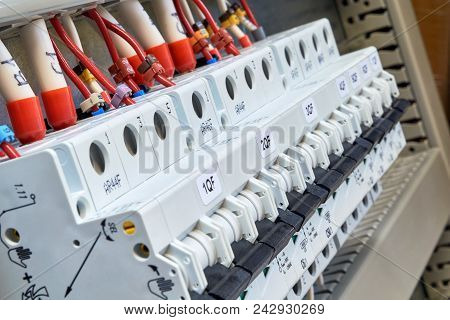 A range of modular circuit breakers in the electrical Cabinet. Wires or cables are connected to the circuit breakers. On the wires are insulated terminals and marking. Modern technology. poster
