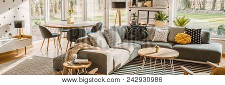 Side Angle Of A Corner Sofa With Pillows, Table And Dining Table With Chairs Behind In A Bright Livi