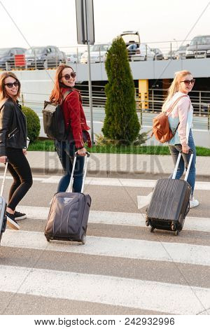 Photo of three happy girls smiling while traveling abroad together carrying luggage to airport. Air travel or holiday concept