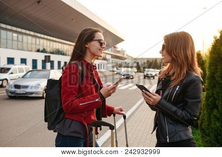Photo of two young women traveling abroad, and communicating with mobile phones in hands while waiting for flight with luggage near airport. Air travel or holiday concept