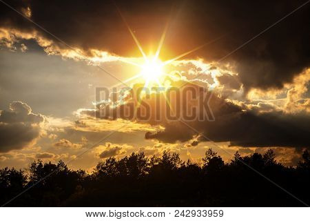 sunset with dark clouds over forest
