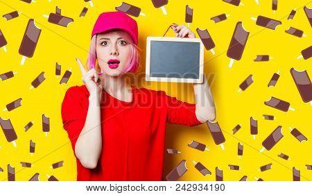 Portrait Of Beautiful Surprised Young Woman With Little Blackboard On The Wonderful Yellow Studio Ba