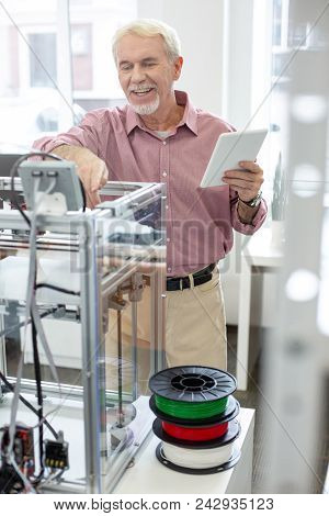 Good Results. Upbeat Senior Man Learning How To Use A 3d Printer And Smiling Cheerfully While Checki