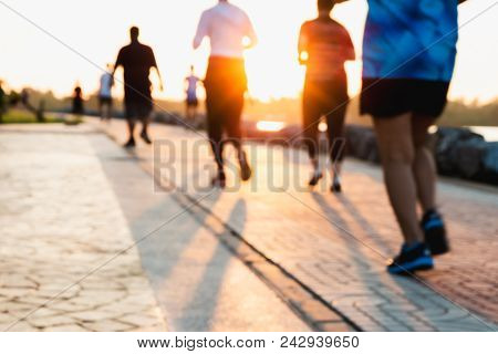 Blurred Group Of Runner Are Running In Park At Evening Sunset.