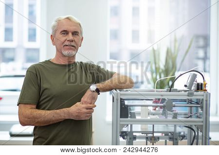 Brand New Device. Upbeat Senior Man Posing Near A 3d Printer And Smiling While Leaning His Elbow On