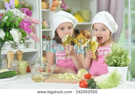 Two Adorable Little Girls In Aprons Eating Bananas At Kitchen