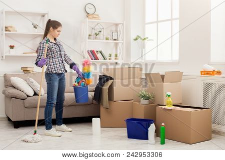 Young Woman With Cleaning Equipment Ready To Clean New House After Moving. Professional Cleaning Ser
