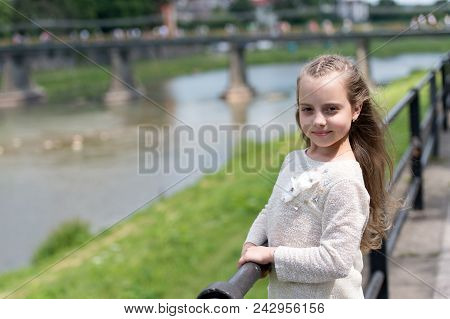 Girl Child Tourist Enjoy Sightseeing While Walks. Kid Girl With Long Hair Walks Near Riverside, Rive