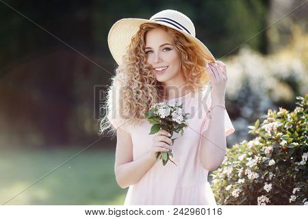 Beautiful Young Model Spring Girl In Flowers With Hairstyle In Summer Blossom Park. Woman In A Bloom