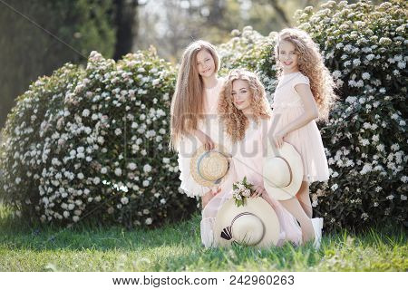 The Older Sister And Her Two Younger Sisters Spend Time Outdoors In A Beautiful Park With Flowering