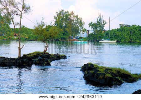 Small Islands Including Volcanic Lava Rocks And Plants With Sail Boats Anchored Beyond Taken In The