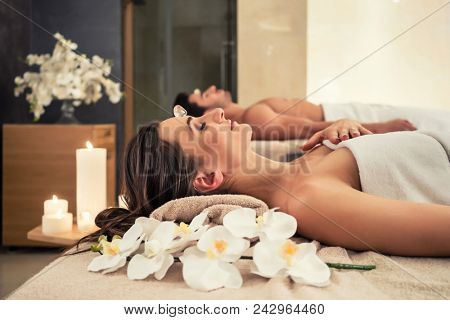 Young man relaxing with his partner on massage beds at modern spa and wellness center