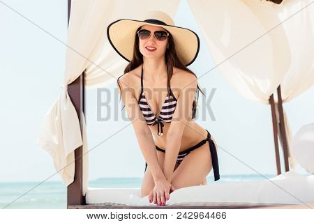 Woman enjoying her beach vacation lounging in sun tent in summer