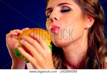 Woman eating burger and winks. Happy student going to seductively eat great sandwich for lunch. Joyful woman offers fast food on black background. She is delighted with new taste of hamburger.