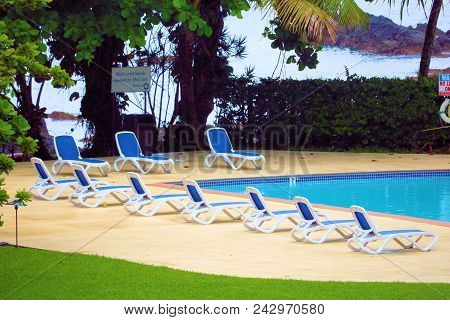 May 15, 2018 In Hilo, Hi:  Pool Surrounded By Lawn Chairs Beside A Lush Garden On The Beach Taken At