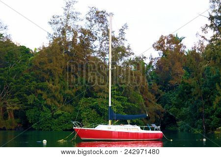 May 18, 2018 In Hilo, Hi:  Sail Boat Anchored Within The Calm Waters At The Hilo Bay Marina Surround