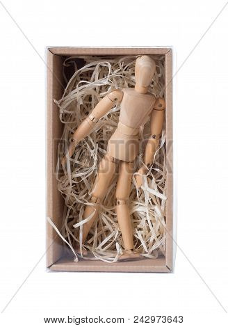 Wooden Mannikin Standing In Closed Cardboard Box Filled With Wood Shred. Concept Of Loneliness, Isol