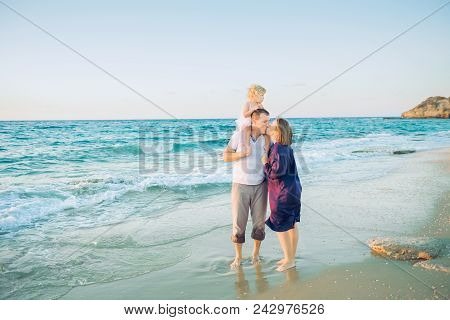 Happy Family Of Three - Pregnant Mother, Father And Daughter Embracing, Laughhing And Having Fun Wal