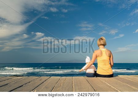 Baby Boy Playing With Mother On The Beach, Summer Day. Supermom With Toddler Son Relaxing On Wooden