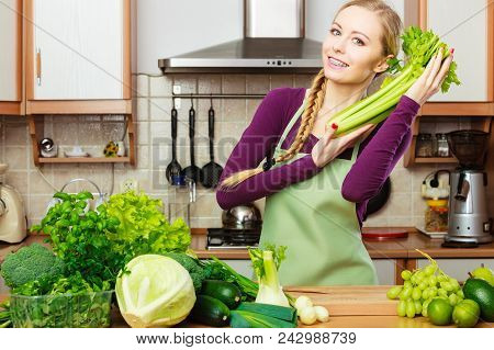 Woman In Kitchen With Many Green Leafy Vegetables, Fresh Produce On Table. Young Blonde Female Addin