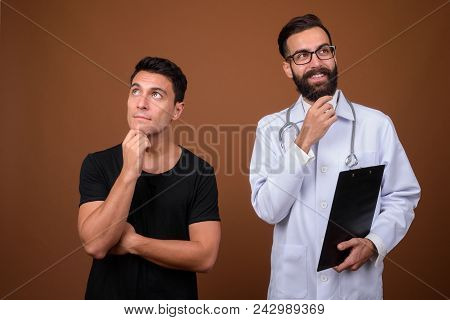 Studio Shot Of Young Handsome Bearded Persian Man Doctor With Young Hispanic Man Patient Against Bro