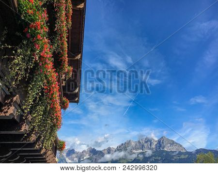 Wooden Balcony Full Of Summer Flowers With Wilder Kaiser Mountains In The Background