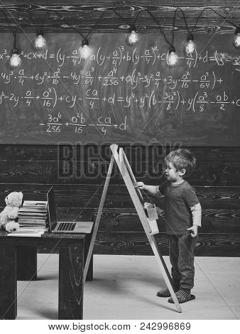 Happy Kid Having Fun. Little Boy Writing On Chalkboard. Side View Kid In Front Of Green Board With M