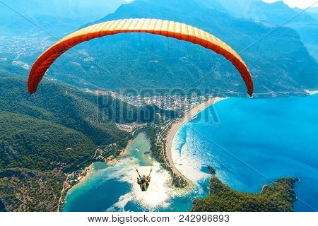 Paragliding In The Sky. Paraglider Tandem Flying Over The Sea With Blue Water And Mountains In Brigh