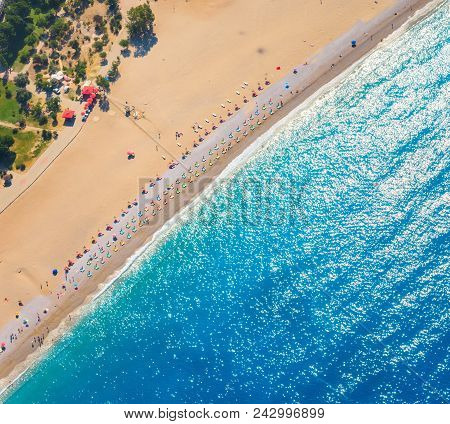 Aerial View Of Sandy Beach With Colorful Chaise-lounges And Blue Sea In Sunny Bright Day In Oludeniz