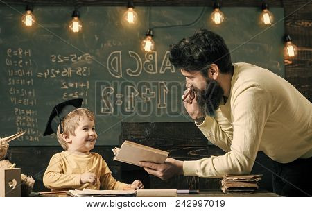 Happy Kid Having Fun. Wunderkind And Genius Concept. Father, Teacher Reading Book, Teaching Kid, Son