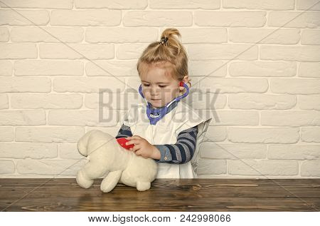 Child Childhood Children Happiness Concept. Child Play Doctor With Teddy Bear On White Wall. Baby Ve