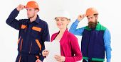 Confident team of workmen and woman standing grouped in their dungarees and hardhats smiling at camera isolated on white poster