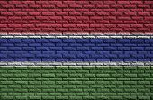 Gambia flag is painted onto an old brick wall poster