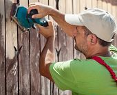 Sideview of worker using vibrating sander machine scraping off old paint from a wooden fence poster