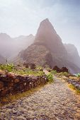 Panoramic view of stony hiking path to Ponta do Sol over amazing arid Aranhas valley with huge mountain peak and house ruins. Santo Antao Island, Cape Verde. poster