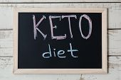 """Blackboard with text """"Keto Diet"""" on wooden background, top view. Ketogenic diet concept, a new trend in slimming. Nutrition concept poster"""