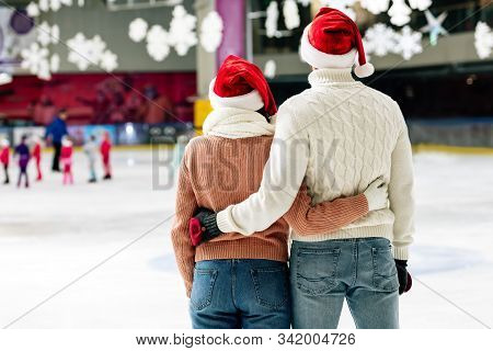 Back View Of Young Couple In Santa Hats Hugging On Skating Rink At Christmastime