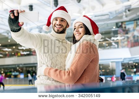 Beautiful Cheerful Couple In Santa Hats Taking Selfie On Smartphone On Skating Rink At Christmastime