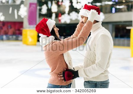 Cheerful Couple In Santa Hats Spending Christmastime On Skating Rink